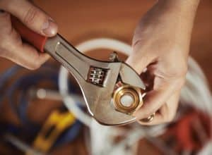 Close-up of plumber hands screwing nut of pipe with wrench over plumbing tools background.